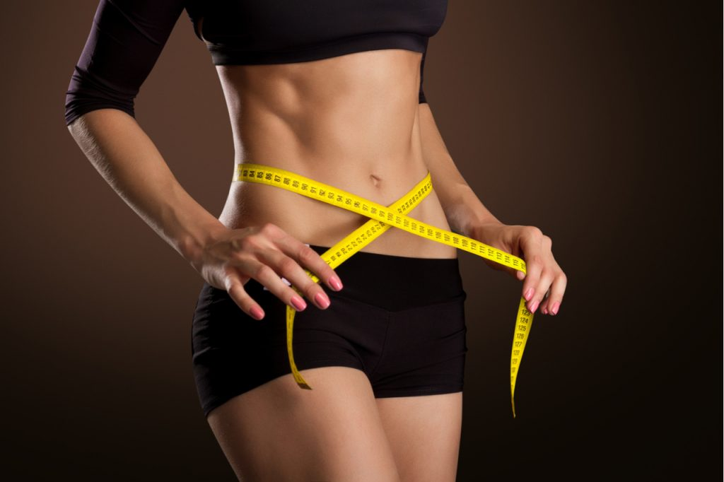 A woman measuring her waistline using a measuring tape. What is the best diet to loss weight?
