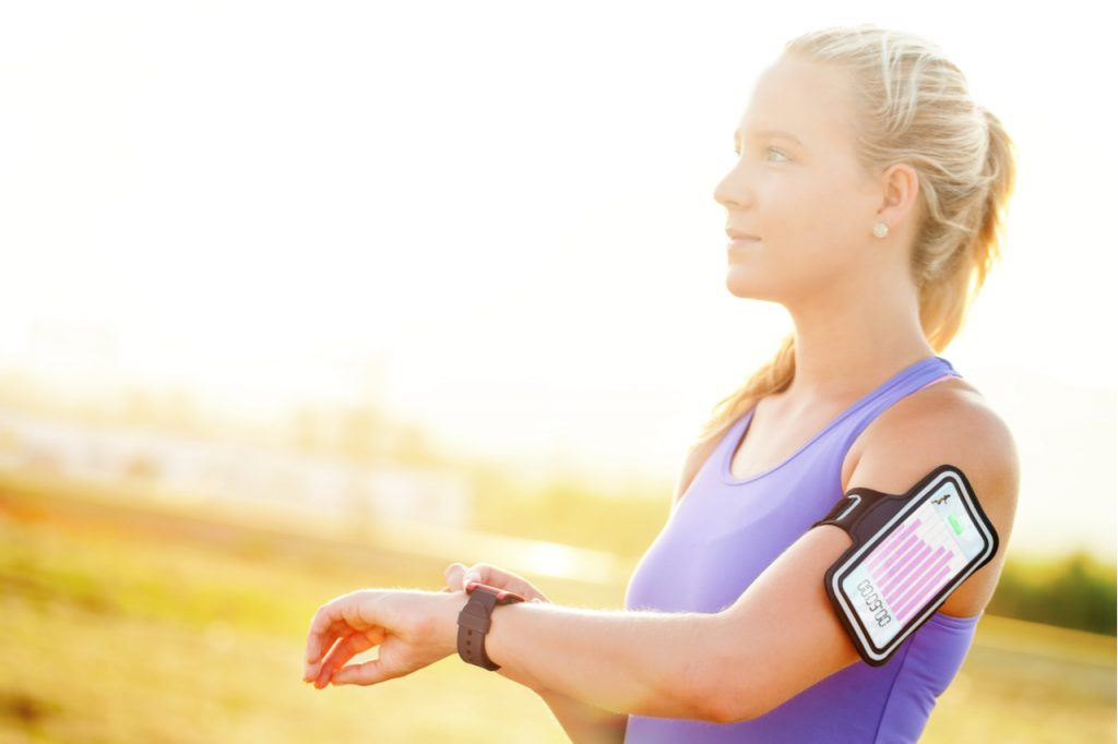 A fit woman checking her watch with a smart phone attached to her arm showing her progress on her run. She is using an app for fitness to track her progress.