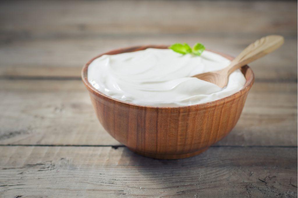 Greek yogurt in a wooden bowl on a rustic wooden table.