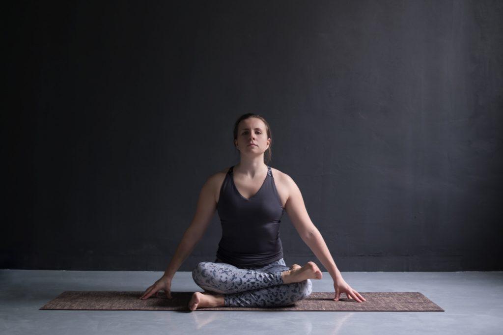 Woman working out, doing yoga exercise on floor agnistambhasana.