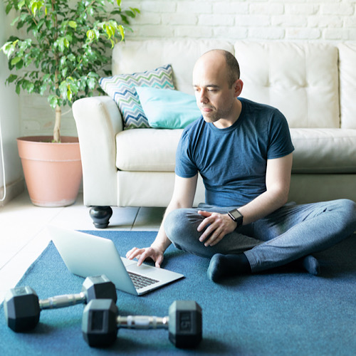 Caucasian bald man looking for some online workouts on a laptop computer and getting ready to exercise and lift some weights at home