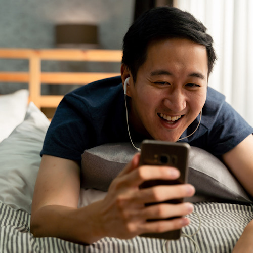 Asian man in casual clothing making facetime video calling with smartphone at home
