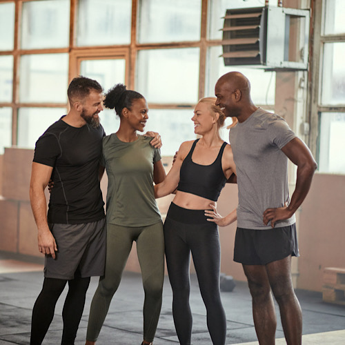 Laughing group of diverse young friends in sportswear talking while standing arm in arm together in a gym after working out