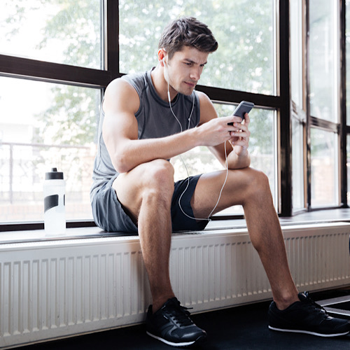 Fitness man wearing sportswear listening to music sitting on windowcill