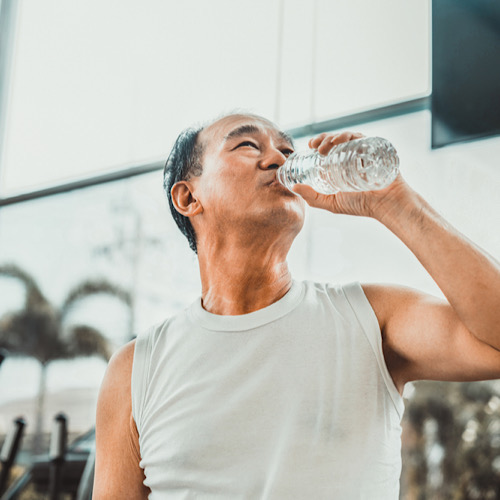 Senior man drink mineral water in gym fitness center after exercise