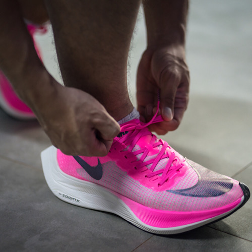 """A runner is wearing Nike """"ZoomX Vaporfly Next%"""" in pink."""