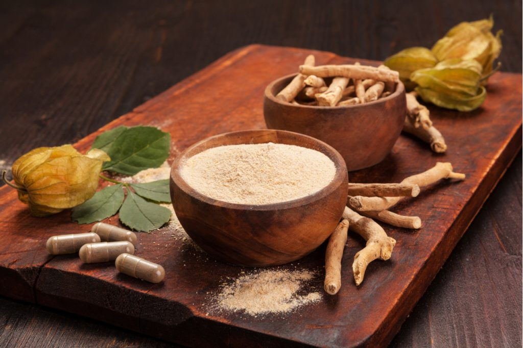 Roots and powder of Ashwagandha also known as Indian ginseng an adaptogenic herb on wooden background.