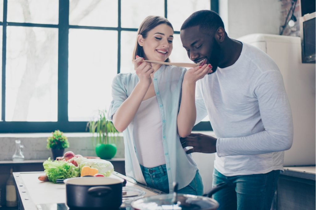 A multi racial couple cooking at the kitchen.