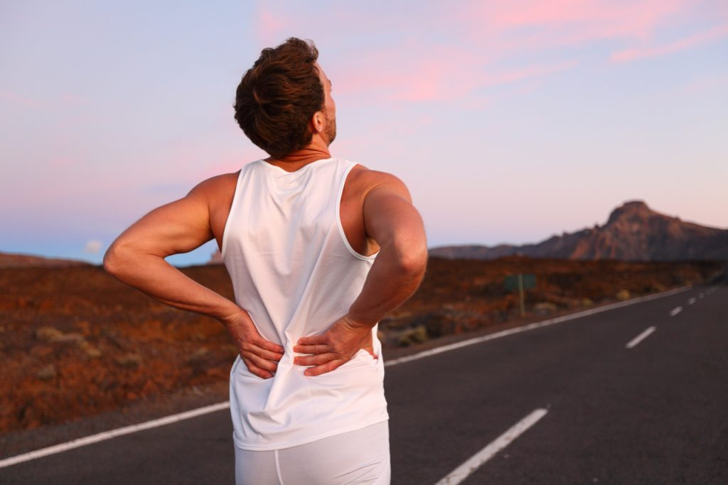 Athletic running man with neck and back pain in sportswear rubbing touching lower back muscles.