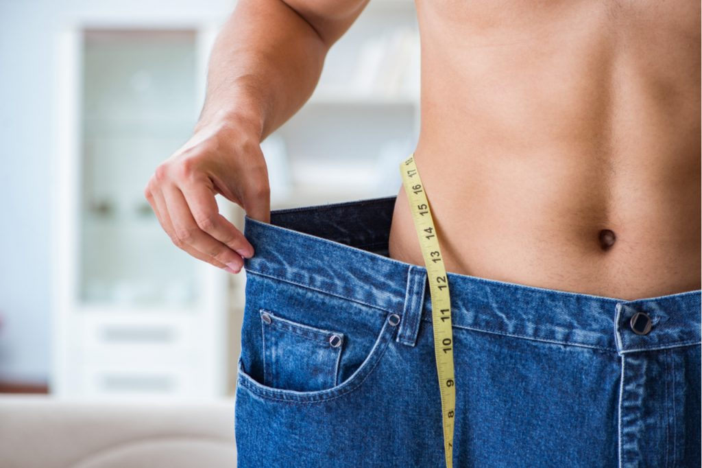 Man in oversized pants with tape measure in weight loss concept.