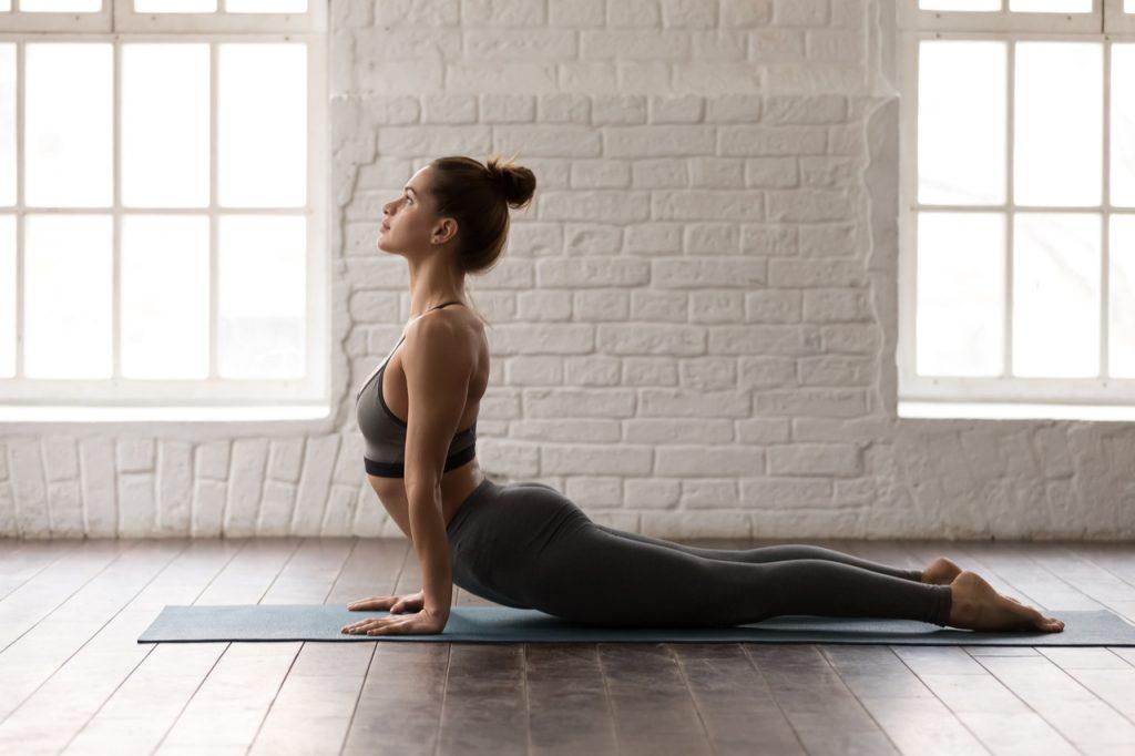 Woman practicing yoga, lying in Cobra pose, doing Bhujangasana pose.