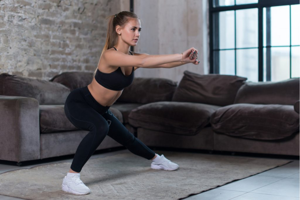 Woman doing home workout performing lateral lunges at home.