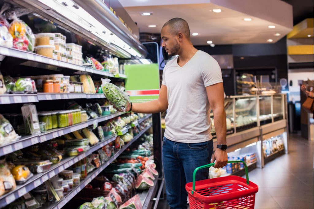 Man buying vegetables in grocery section at supermarket.