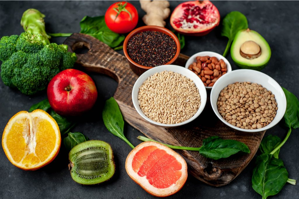 Complex carbohydrates like whole grains in bowls, nuts, oranges, kiwi, apple, avocado, pomegranate, broccoli and tomato.
