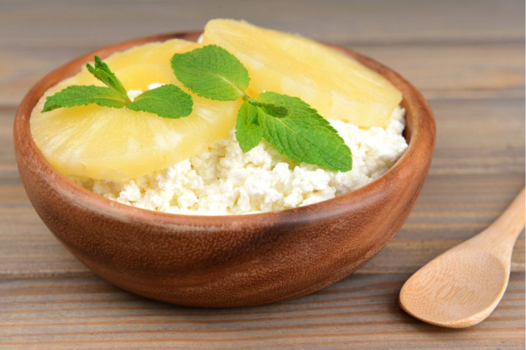 Cottage cheese and 2 slices of pineapple with mint leaves on wooden bowl and a wooden spoon on the side.