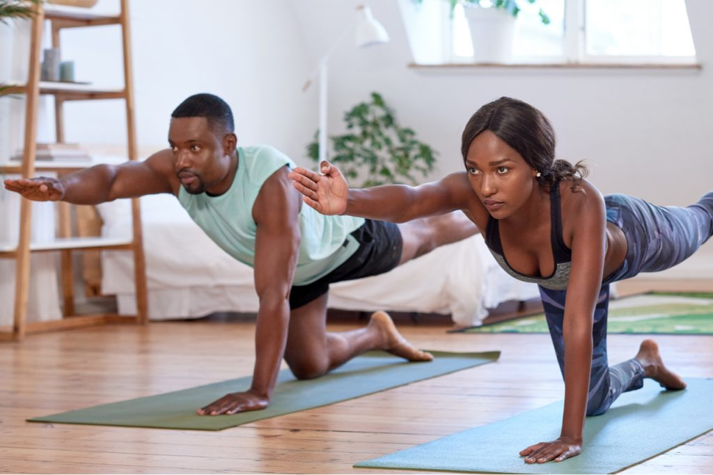 An African American couple doing yoga at home.