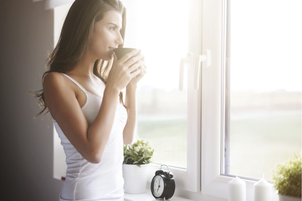 A woman drinking coffee in the morning while looking at the window.