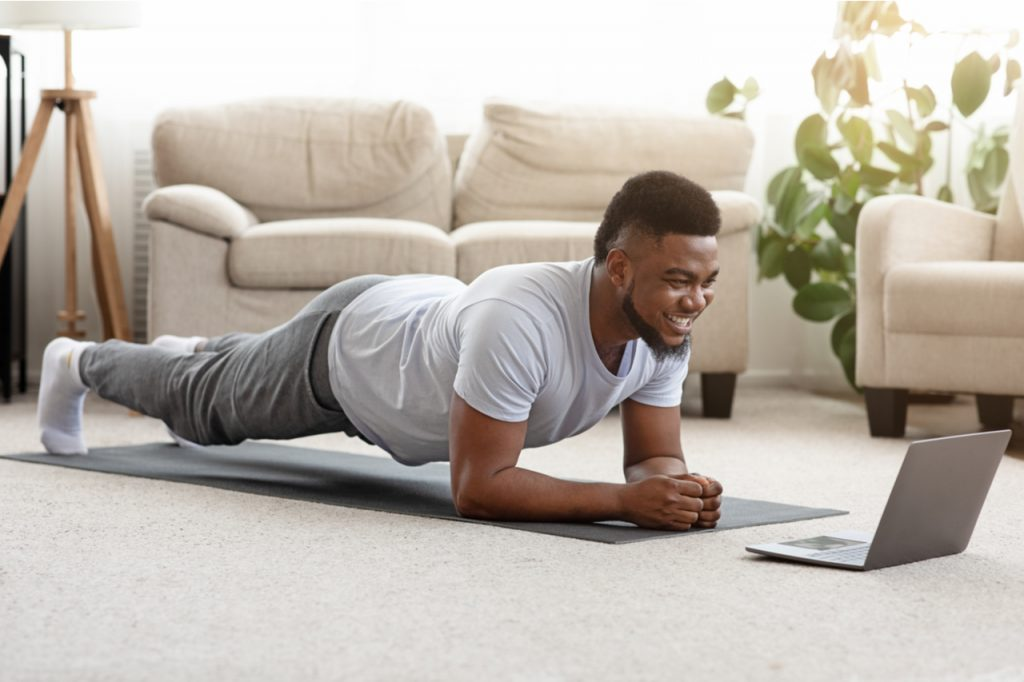 Sporty man doing yoga plank while looking at his laptop as workout motivation in his living room.