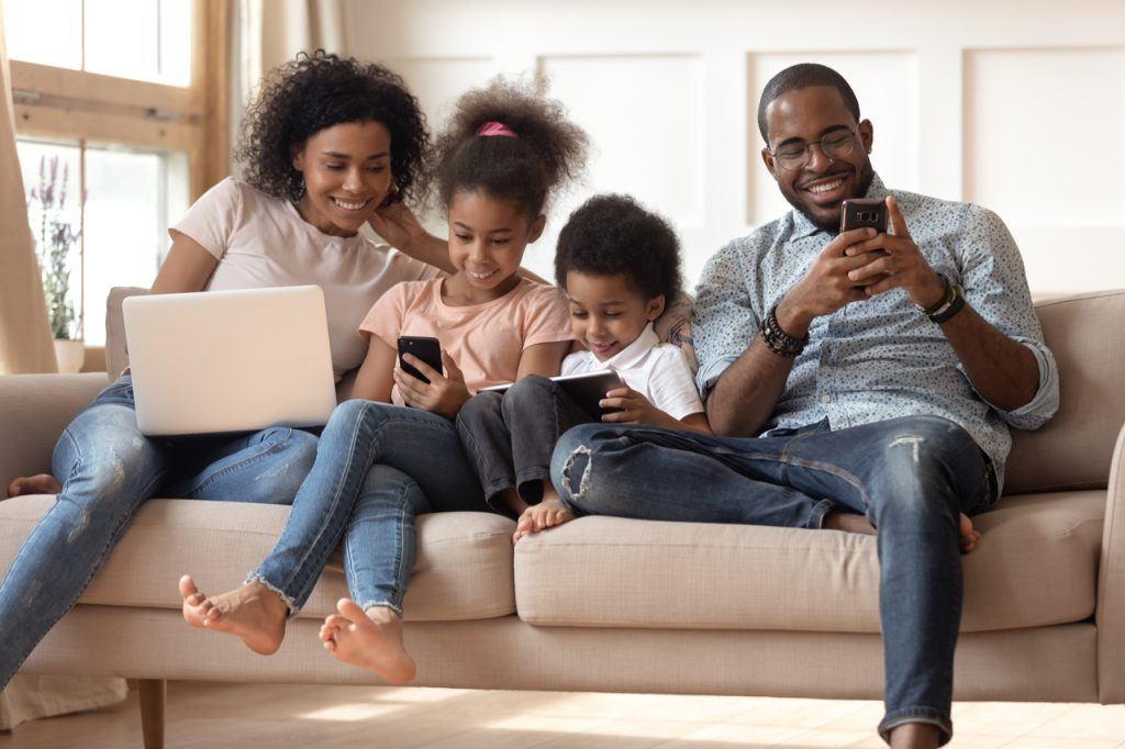 An african american family happily bonding at home. Kids spending time with their parents to celebrate parent's day.