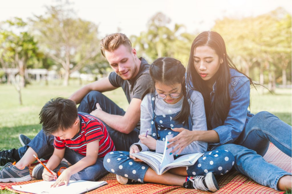 Parents helping their children with their homework while outdoors, showing a relaxed atmosphere.