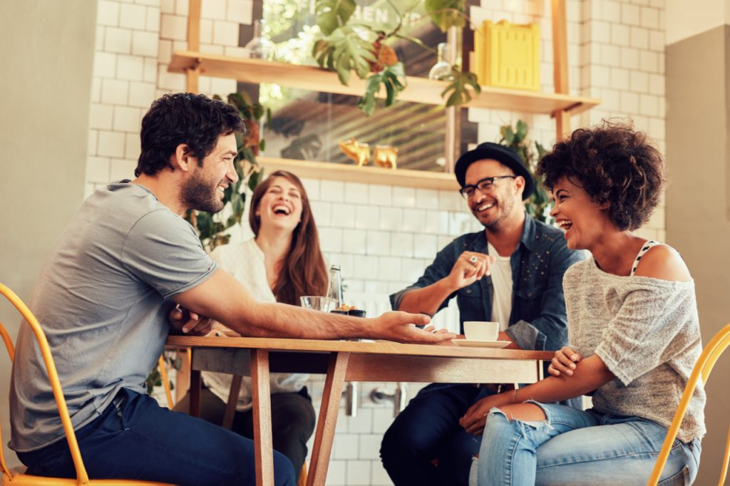 A group of friends having a good laugh while having a coffee. What is social wellness and how it can affect you?
