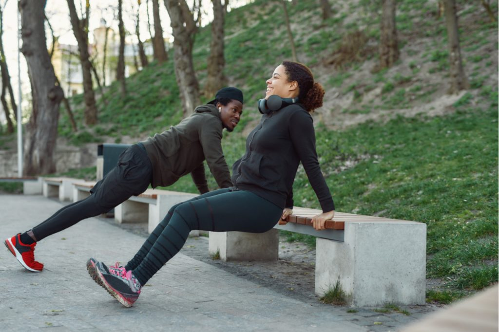Couple working out in park outdoors.