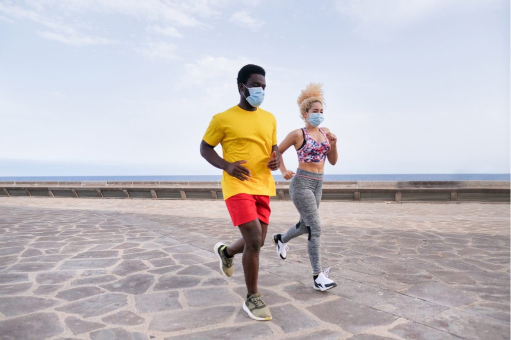 Young active couple do sports together and wearing protective face mask.