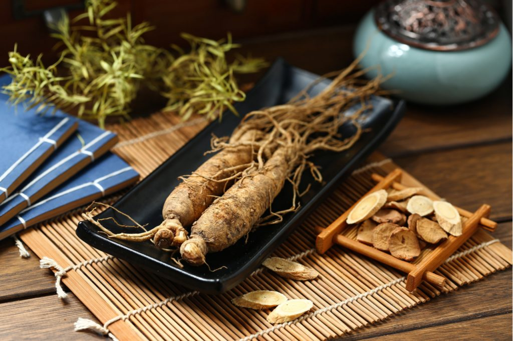 Ginseng in black plate on wooden table.