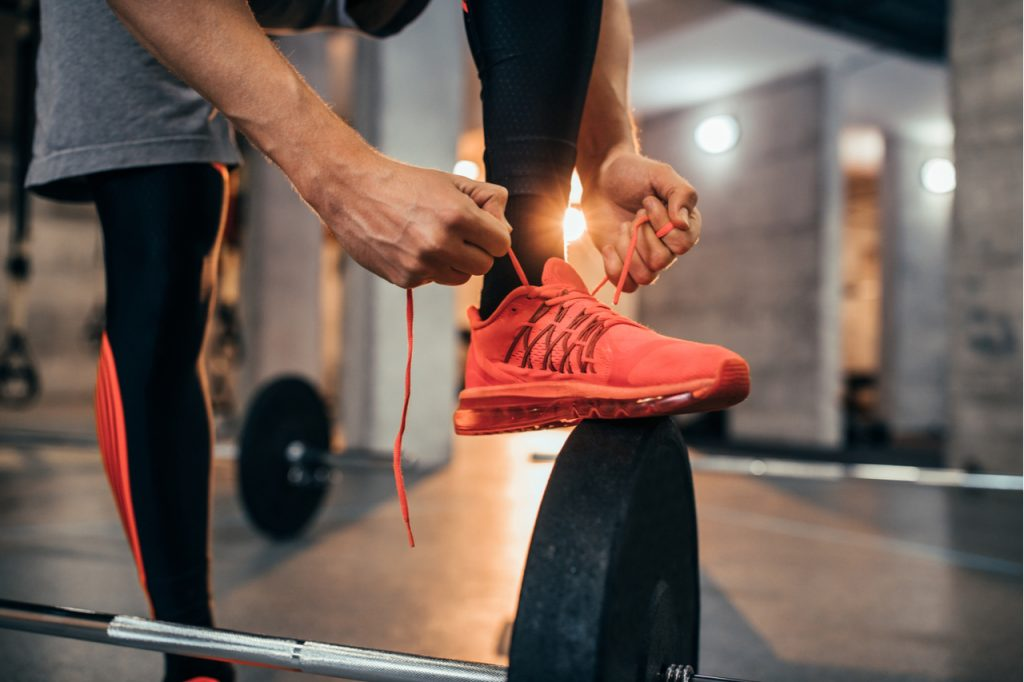 A man tying his shoe laces while stepping on a barbell plate.