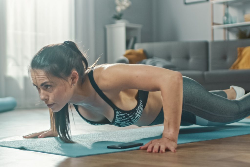A sporty woman training at home in her living room with full body workout plan.