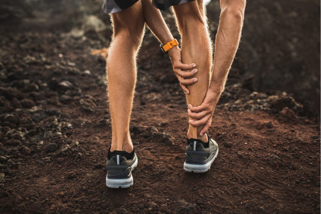 Male runner holding injured calf muscle and suffering with pain.