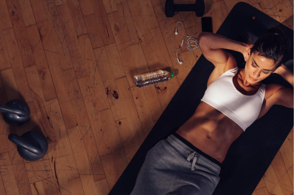 Overhead view of female doing abs workout at the gym.