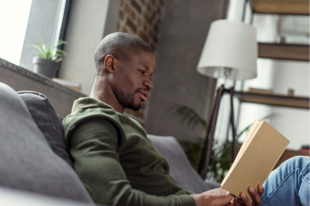 An African American man who is reading a book while sitting on the couch. What is intellectual wellness?