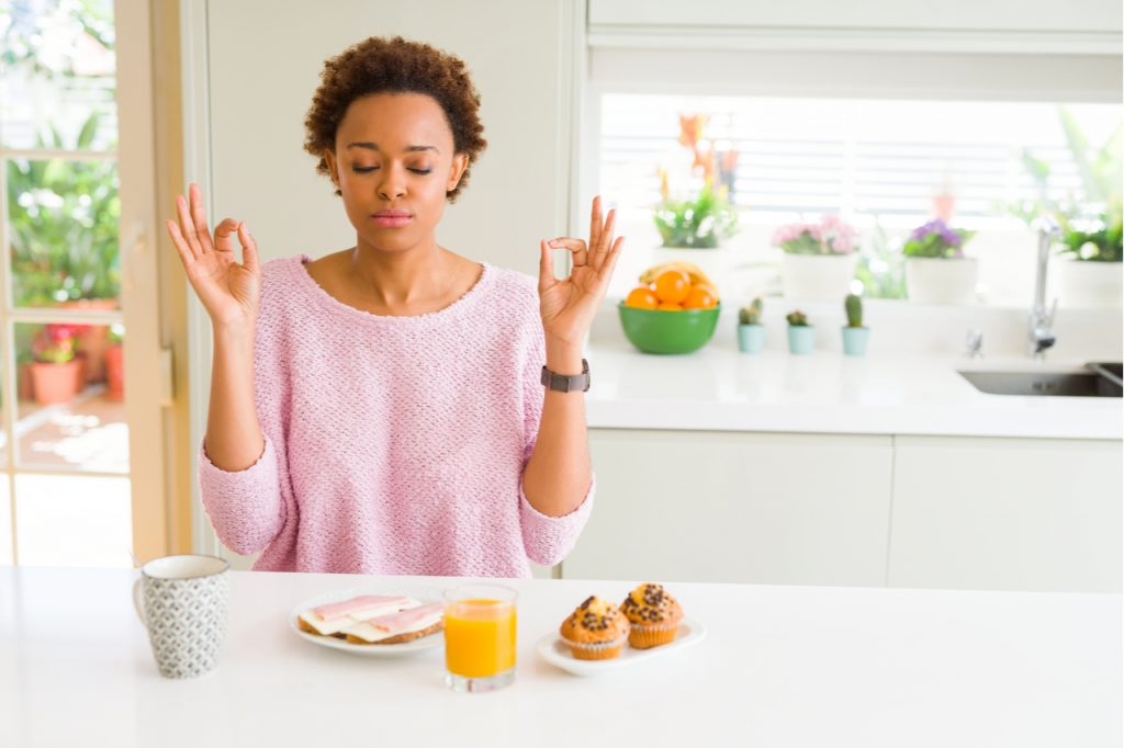 A young Afro American doing meditative eating, with food and drinks on the table. She is motivating herself on how to eat healthy.