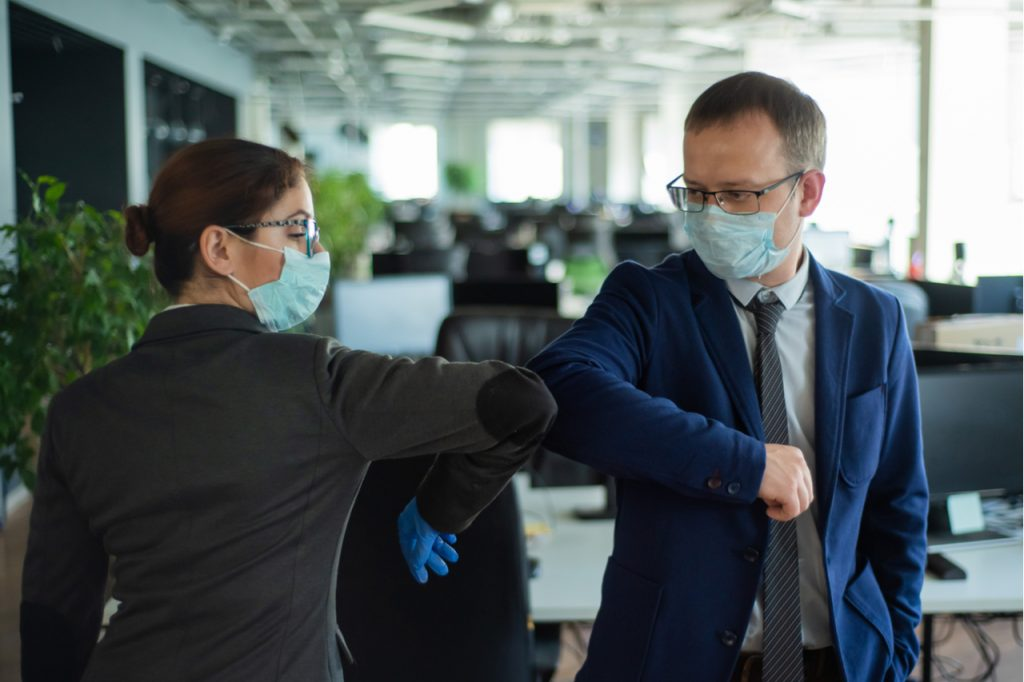 A man and a woman in medical masks maintain a social distance at work.