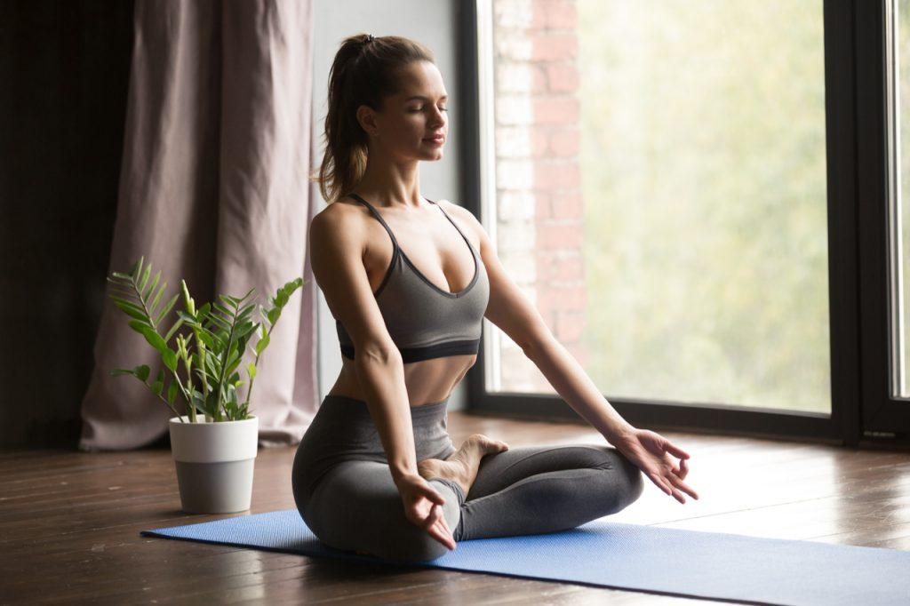 Woman practicing yoga, doing Ardha Padmasana pose.