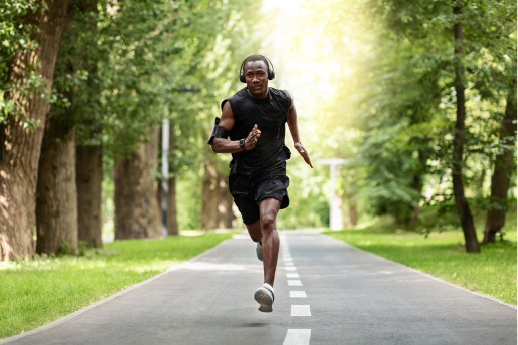 An African American doing his daily run while wearing a headphone.