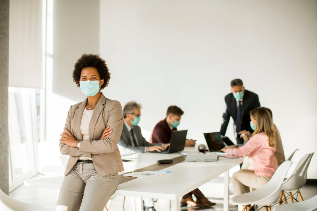 Woman in the office wear mask as protection from corona virus.