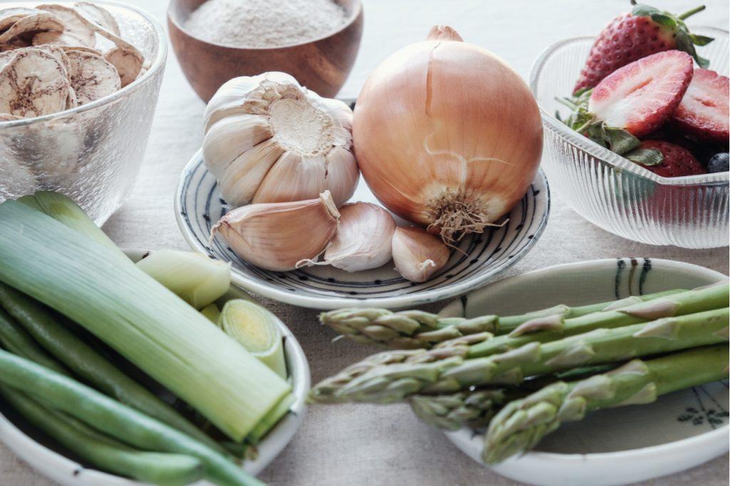 Onions, garlic cloves, leaks, asparagus, sliced strawberry and a bowl of mushroom.