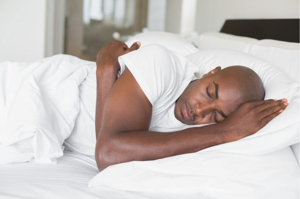 An African American man sleeping soundly on his bed.