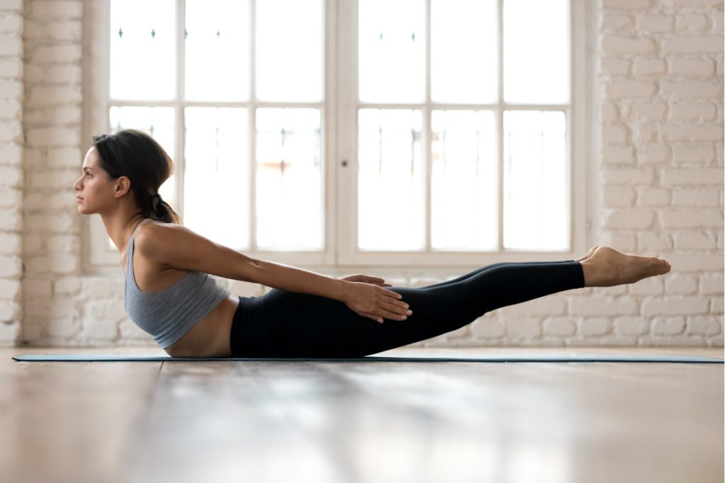 Woman practicing yoga, doing Double Leg Kicks pose.