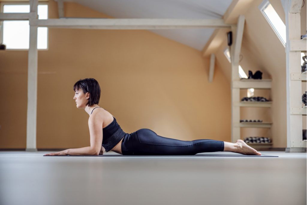 Woman with brown hair in Sphinx yoga pose.