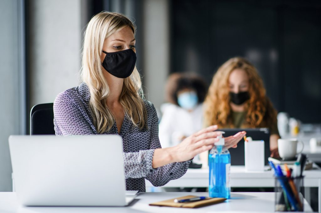 Woman with face mask back at work in office after lockdown, disinfecting hands as part of workplace safety measures.