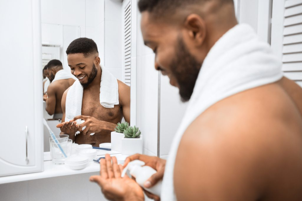 Man doing self care routine squeezing cream on his hand.