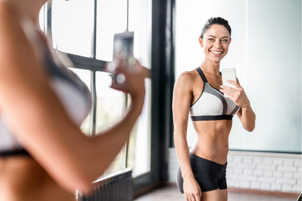 Proud muscular woman smiling boasting her fit figure and slim waist taking selfie in gym mirror.