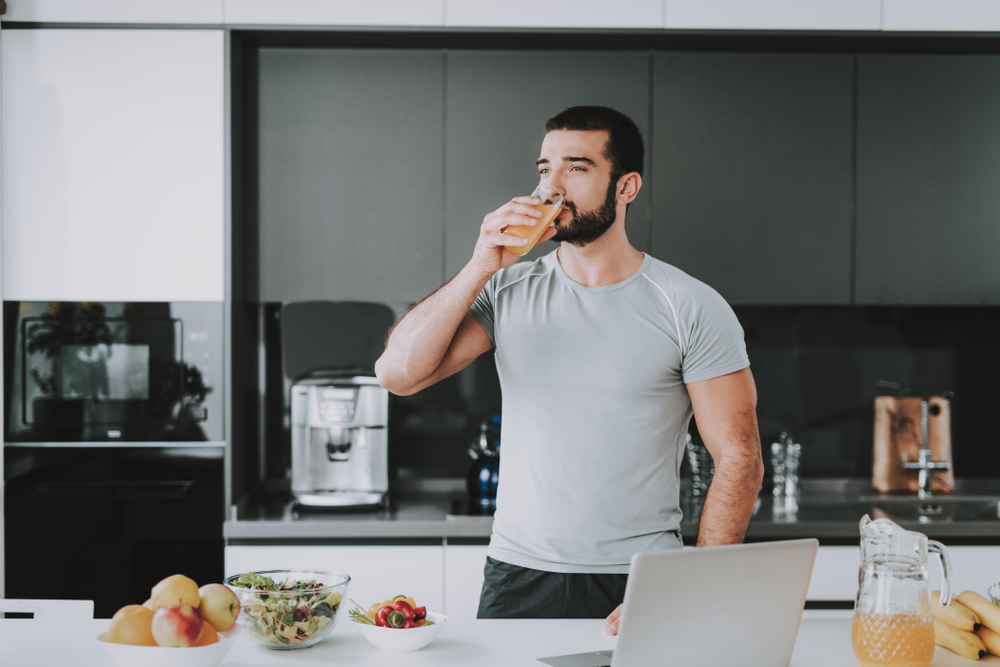 Athletic Man Drinks Fresh Juice On The Kitchen.