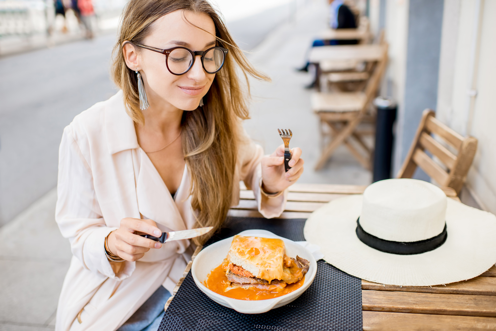 Woman eating traditional portuguese sandwich with meat called francesinha sitting at the restaurant in Porto city, Portugal