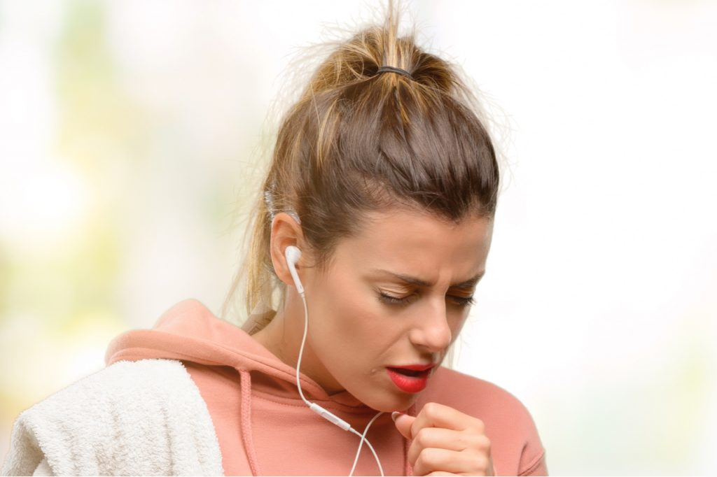 Young sport woman wearing workout sweatshirt sick and coughing with weak immune system.