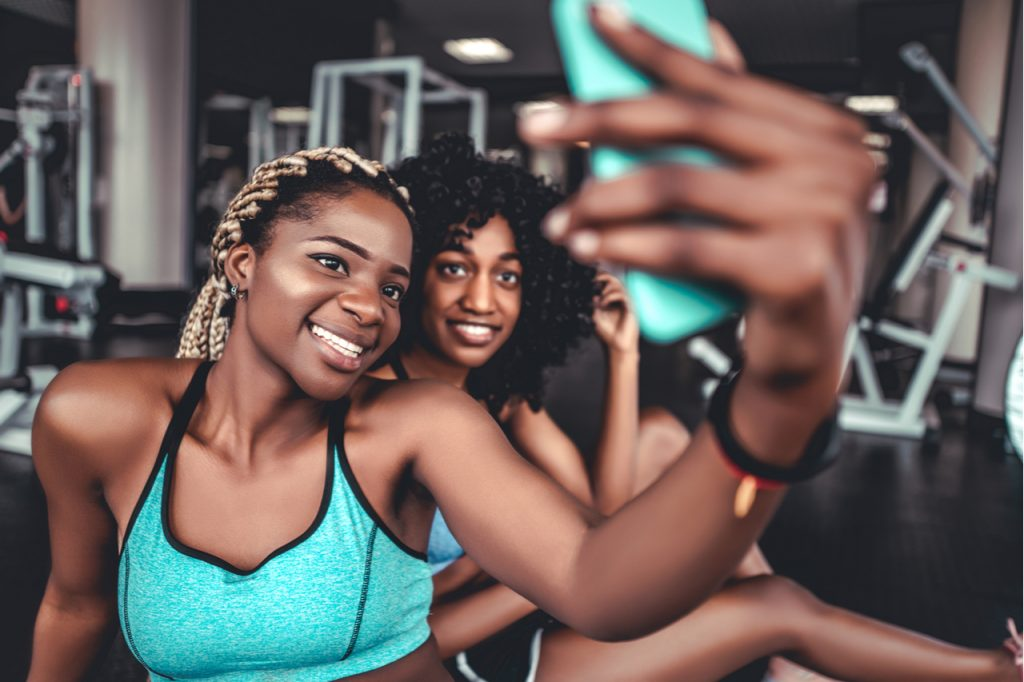 Two smiling beautiful girls in the gym do selfie embracing the digital life.