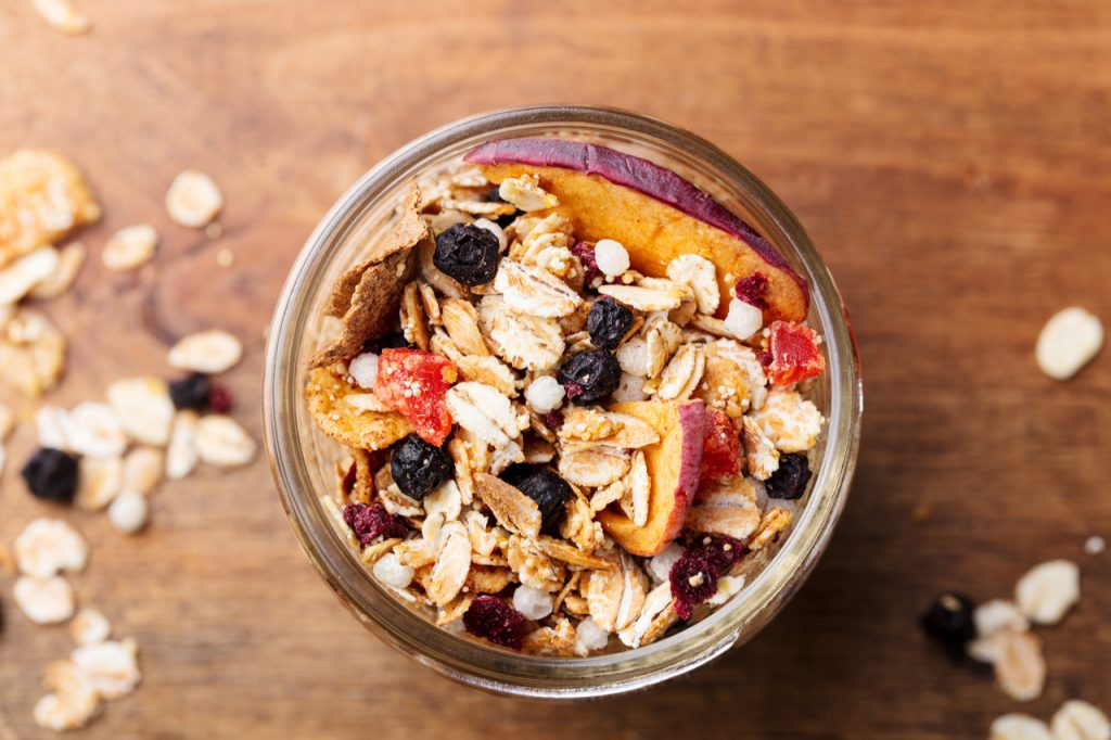 A granola jar with nuts, sliced apples and oats a good source of dietary fiber.